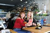 pretty girls taking a selfie in cafe