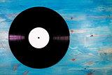 Black color vinyl record on blue wooden background