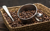Roasted coffee beans inside a basket on a wood background