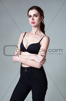 Studio fashion shot (model test): portrait of lovely young girl in pants and bra