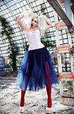 Portrait of cute strange freak girl. Attractive weird woman wearing motley corset, tights and tutu skirt in ruined place. Odd fashion