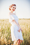 Portrait of cute smiling young woman wearing white dress in field