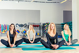 women do yoga, perform stretching exercises on mats