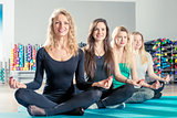 charming girls sit in a lotus position during a yoga training se