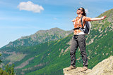 portrait of a happy woman conquering a high mountain with a back