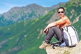 active tourist sits on a rock in the mountains with a backpack,