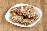Oatmeal cookies with sesame seeds in a white dish on a wooden ba