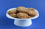 Oatmeal cookies with sesame seeds in a white dish on a violet ba