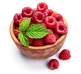 Fresh raspberry in wooden dish with green