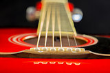 Acoustic red guitar lies on the table, dark background mode with a copy of the hands of space, playing on the classic Spanish, close-up of fretboard and strings, instrument deck, Wallpaper
