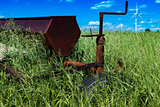 Vintage farming disc harrow in a field surrounded by tall grass with wind turbines