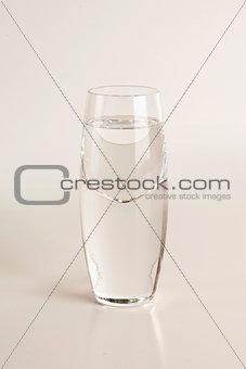 Glass of vodka on light gray background