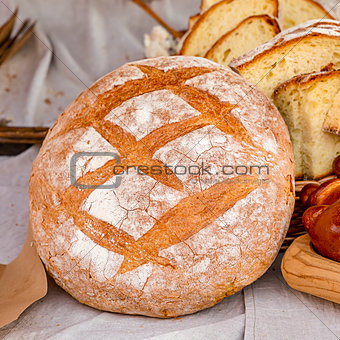 delicious fresh baked rustic bread round bun rolled up with flour on the background of chopped pieces of rustic design culinary
