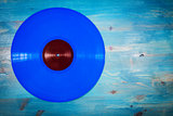Blue color vinyl record on blue wooden background