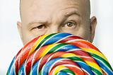 Man Peeking Out From Behind A Lollipop