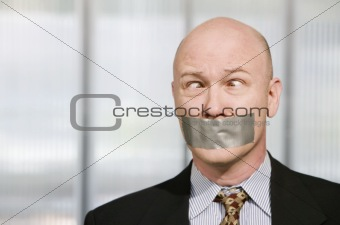 Cross-eyed businessman muzzled with duct tape