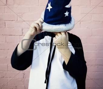 Little boy in a sorcerer hat picks his nose