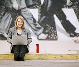 Woman with laptop on a sidewalk