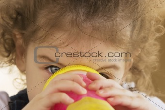 Little girl drinking from a pink cup