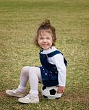 Little girl sitting on a soccer ball.