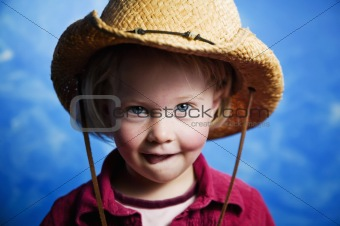 Little girl in front of blue wall with a cowboy hat