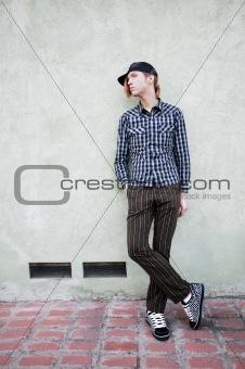 Boy leaning against a green wall