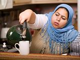 Muslim woman pouring tea