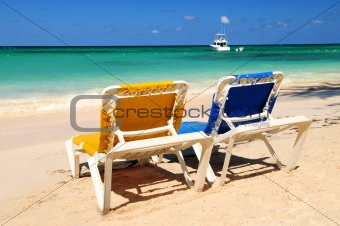 Chairs on sandy tropical beach