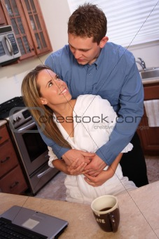 young couple on a kitchen with laptop