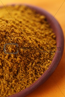 pile of bright Madras Curry Powder in teracotta dish on orange b