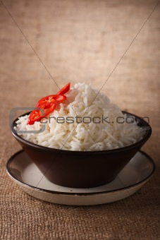 rice bowl with fresh chillies on brown rustic background,