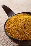 Madras Curry Powder in coconut bowl on hessian background