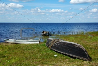 Three old wooden boats on the lake bank