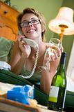Woman at home on phone drinking wine