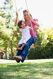 Mother and daughter on garden swing