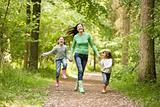 Mother running along woodland path with 2 children
