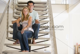 Couple at home sitting on stairs