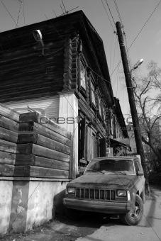Car near old wooden house.