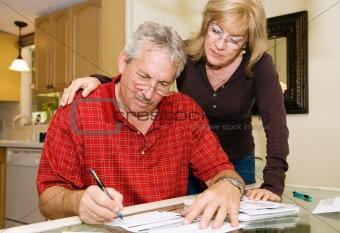 Mature Couple - Signing Paperwork