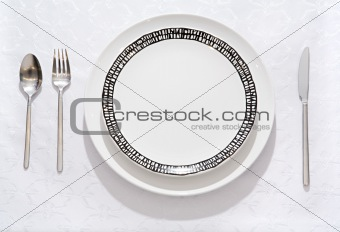 Fork, spoon, knife, empty plate on a table