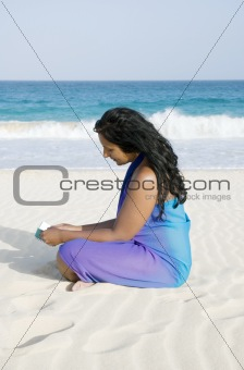 Beautiful asian girl reading on beach.