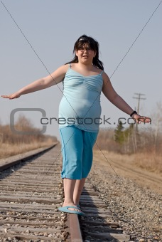 Girl Balancing On Railroad Tracks