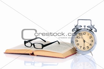 book with alarm clock and eyeglasses