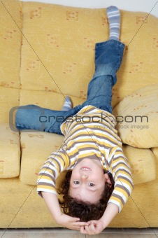 Boy lying down on the sofa at home