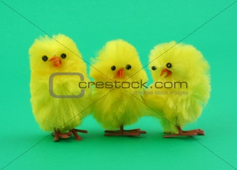 three easter toy chickens on green