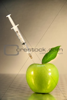 Close-up of syringe in green apple