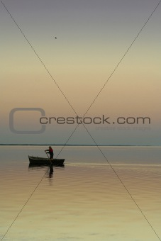 Lonely boat on silent water. sunset