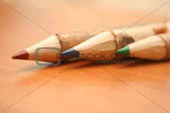 Three pencils lay on a table