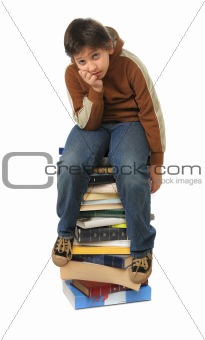 Boy sitting on a big pile of books