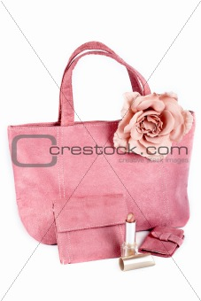 Assortment of pink handbags and lipstick